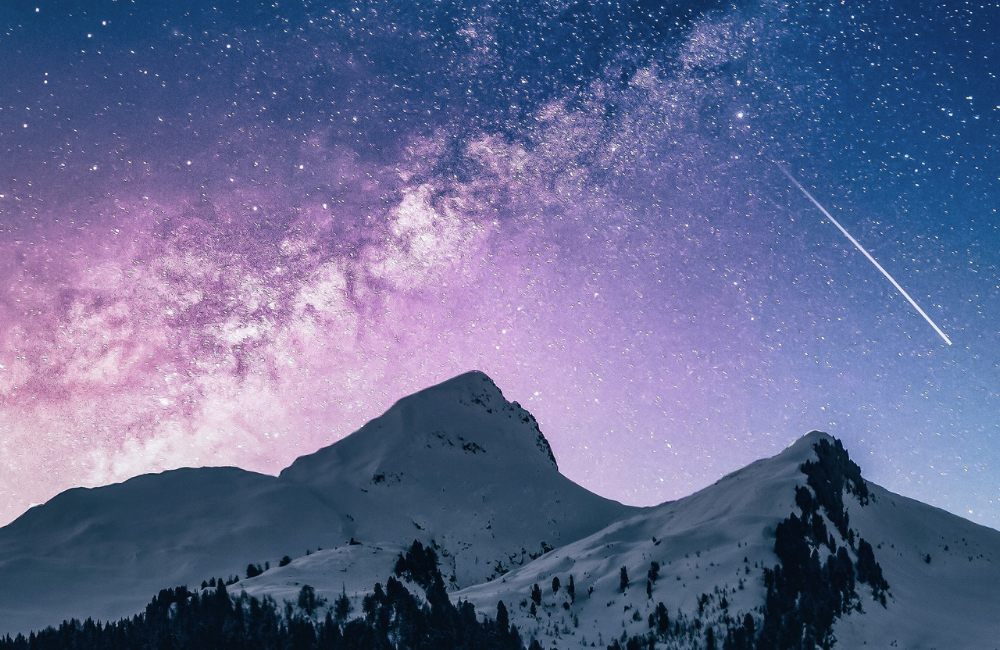Landscape Astrophotography a night sky with pink and blue tones filled filled with stars over a snow capped mountain range
