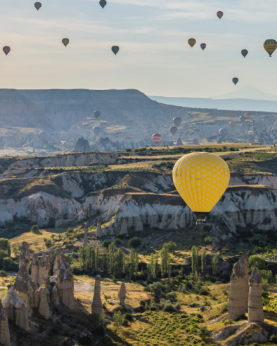 a group of hot air balloons floating through Turkey